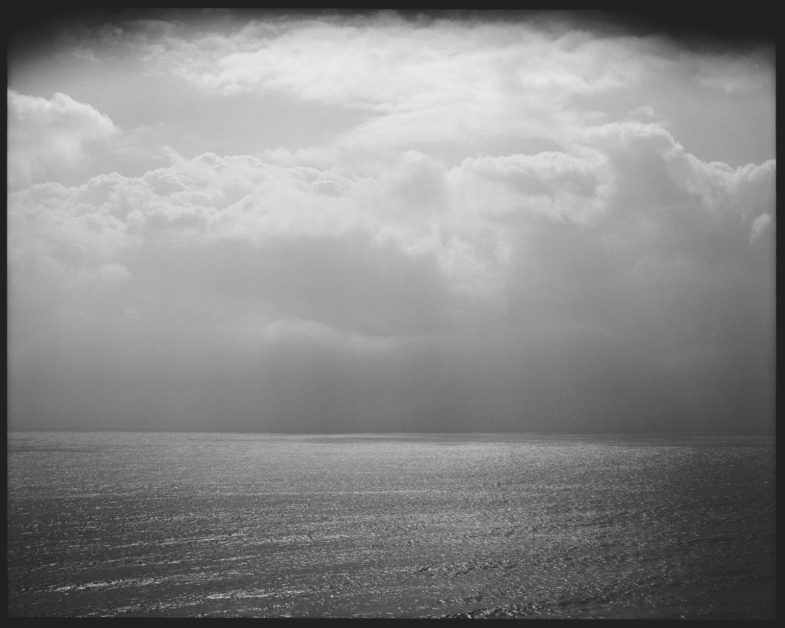 black and white ocean photograph with backlit sun